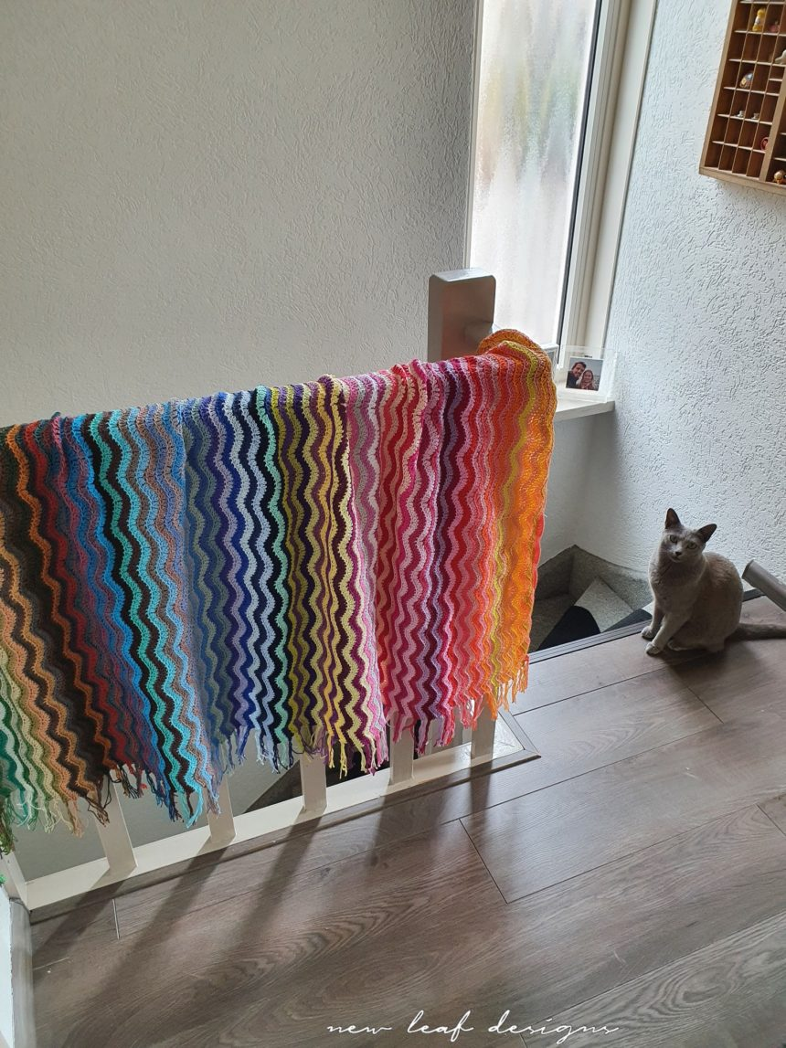 rainbow sea waves blanket hanging over staircase railing