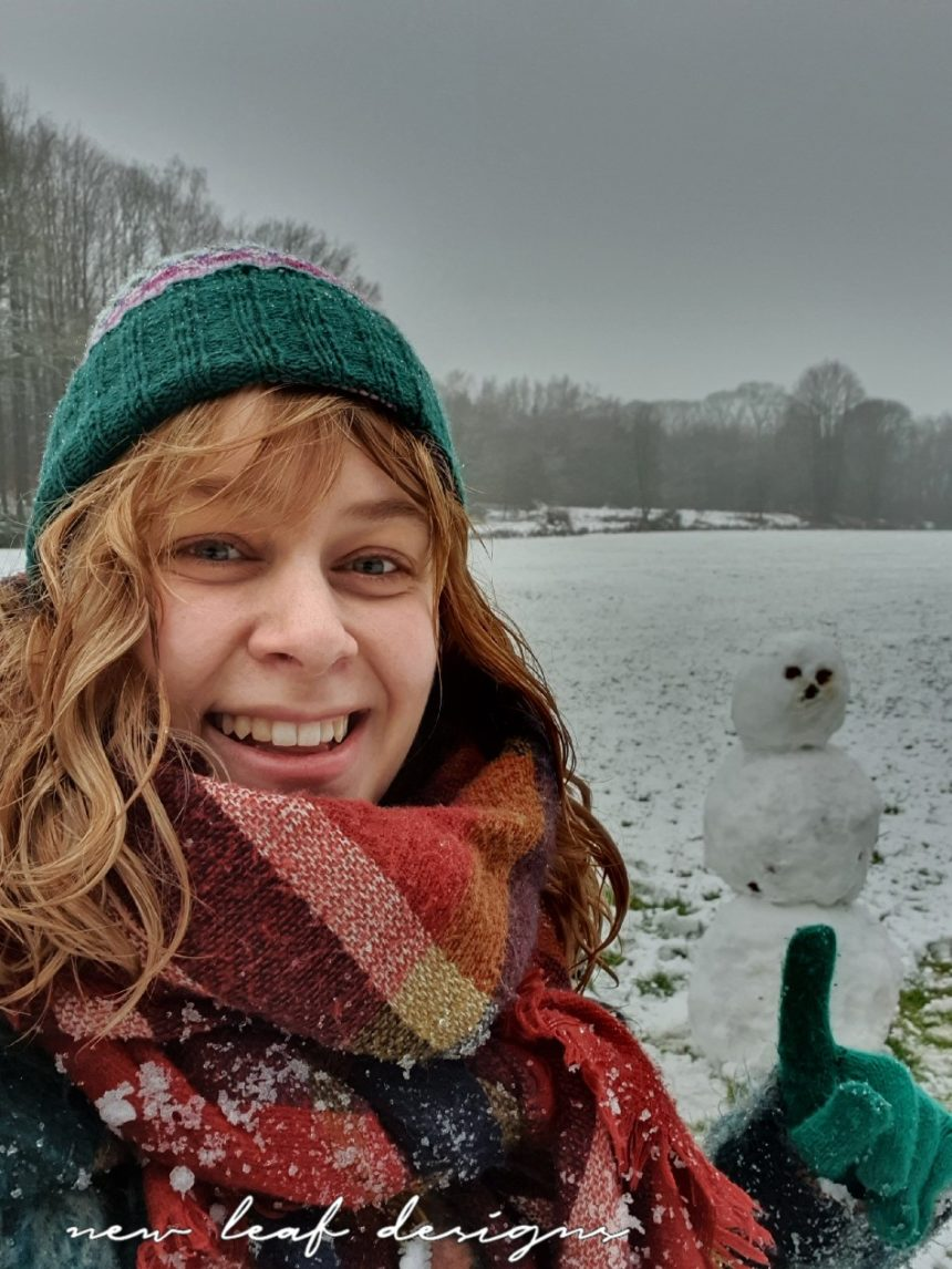 Carmen laughing at the camera and pointing at snowman behind her