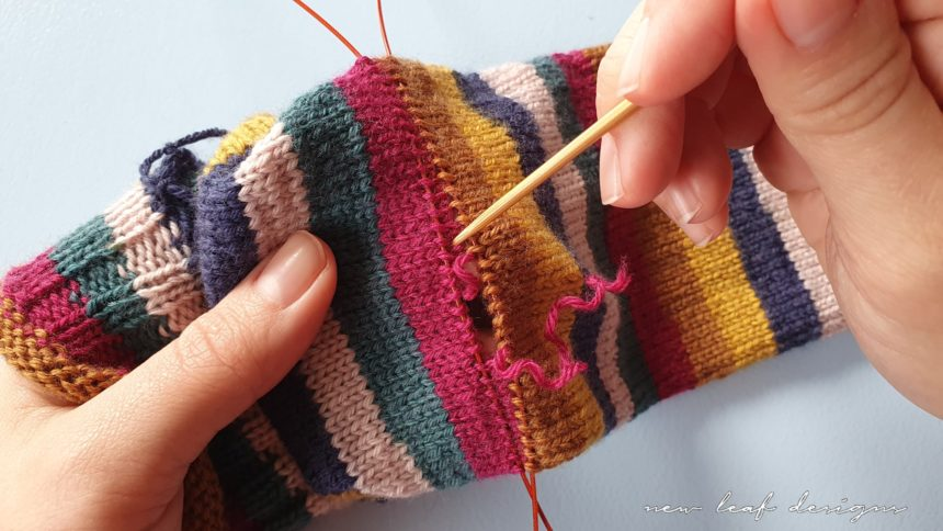 two hands holding sock tube, slowly unraveling yarn to create a gap for the heel