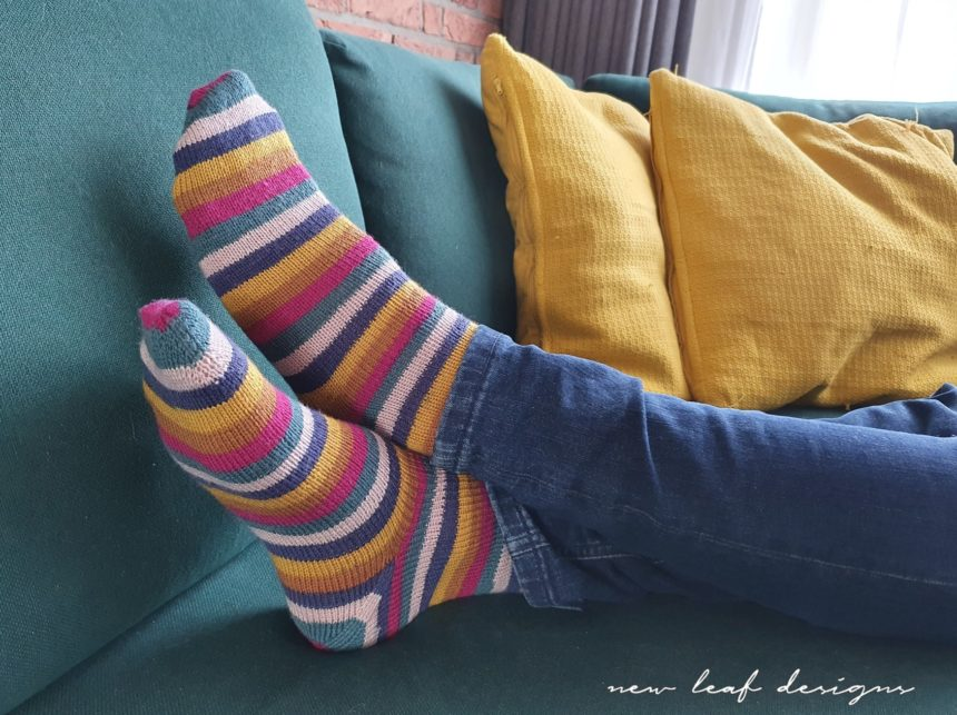 Close up of two feet wearing City Stripe Socks. Feet are casually crossed, lying on sofa. Sofa cushions match the colours used in the socks.