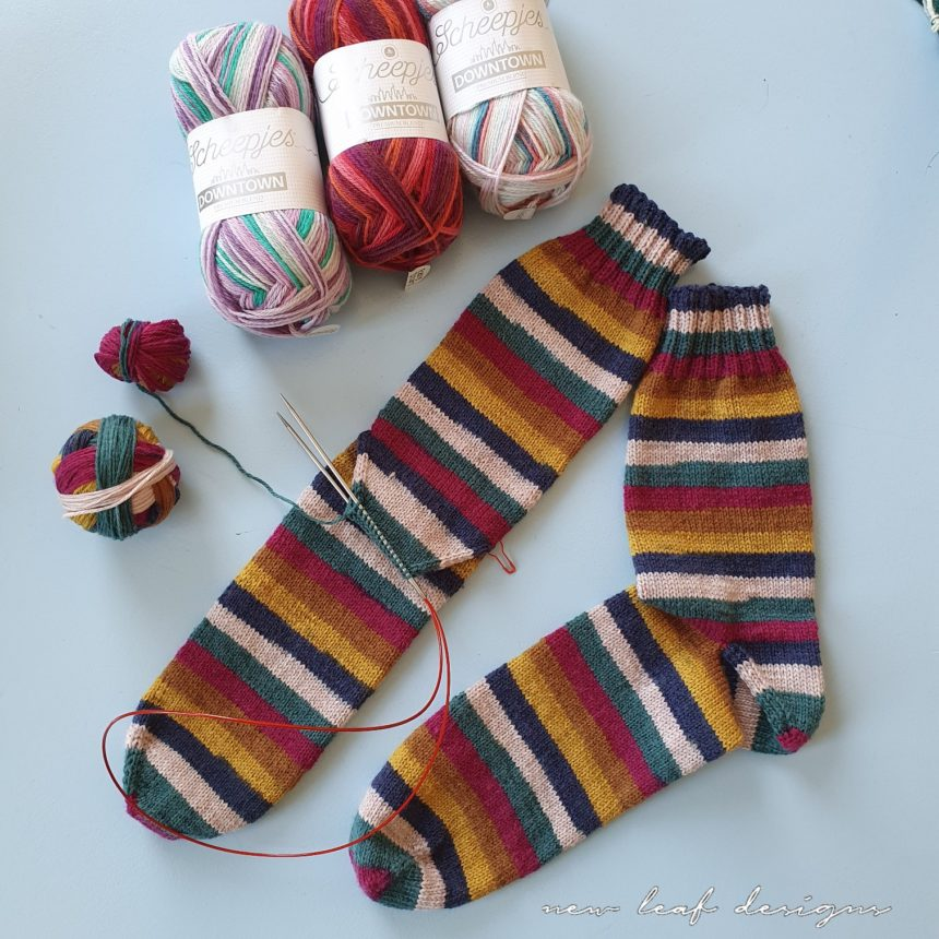 two socks laying on a flat surface, with some balls of yarn laying around them. One sock is finished, while the other sock still has an afterthought heel in progress
