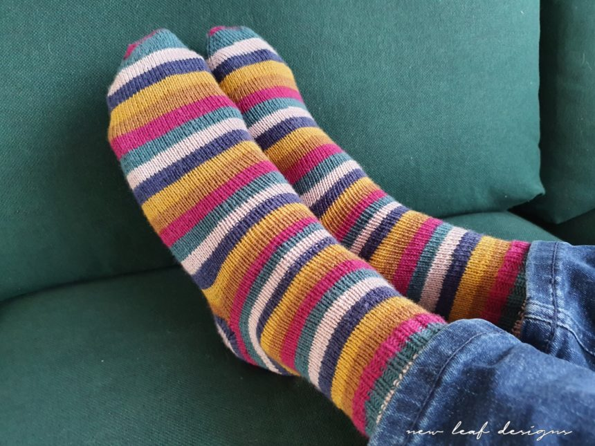 Two feet wearing City Stripe Socks, lying on sofa cushion.