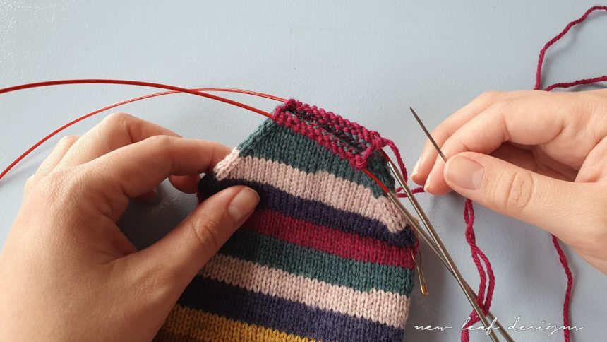two hands holding up sock in progress, with tapestry needle ready for sewing